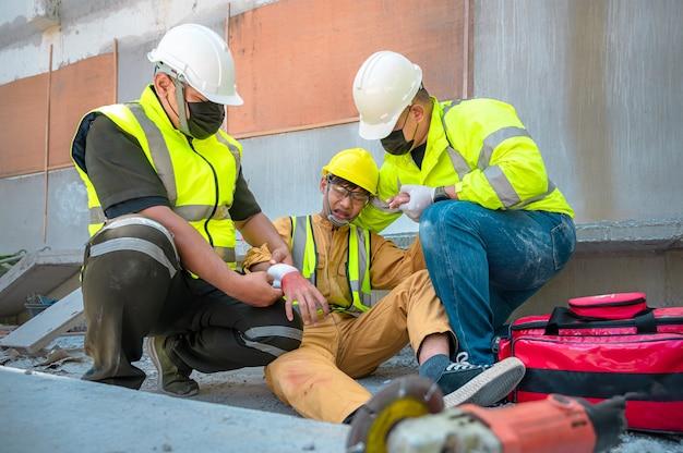Trabalhador da construção civil sofre um acidente em uma construção. engenheiros de ajuda de emergência prestam primeiros socorros a trabalhadores da construção em acidentes. equipe de segurança ajuda um operário da construção civil que sofre um acidente.