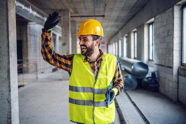 Trabalhador da construção civil sorridente positivo no desgaste do trabalho em pé no prédio e acenando para seu colega. edifício no interior do processo de construção.