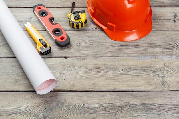 Trabalhador da construção civil suprimentos e instrumentos na mesa de madeira