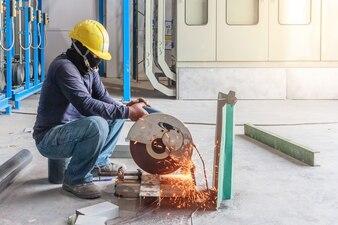 Trabalhador da construção civil trabalhando em cortar um metal e aço com serra de esquadria composta