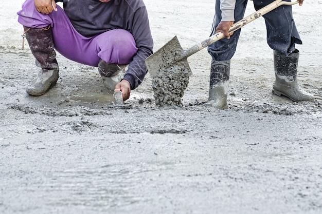 Trabalhador da construção civil trabalhando no cimento de gesso para o chão em casa nova.
