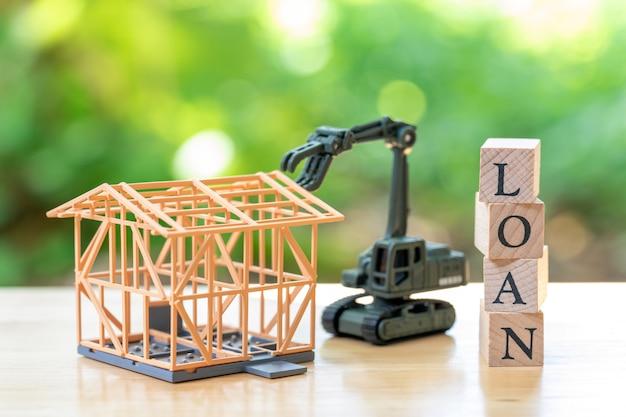 Trabalhador da construção civil um modelo de casa modelo é colocado com palavra de madeira