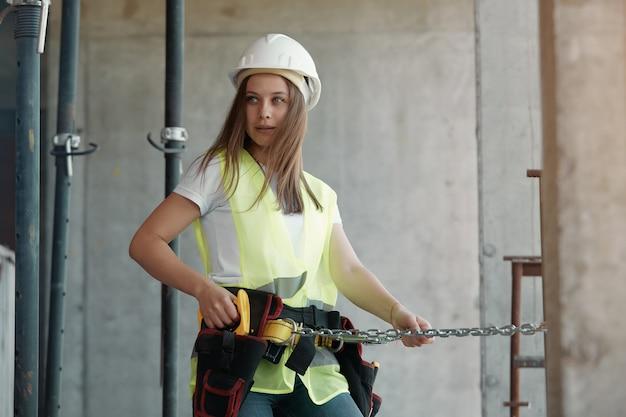 Trabalhador da construção civil, uma garota com um colete verde protetor e um capacete branco usa cintos de segurança enquanto trabalhava em um novo projeto de canteiro de obras.