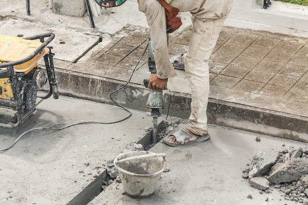 Trabalhador da construção civil usando britadeira perfurando superfície de concreto