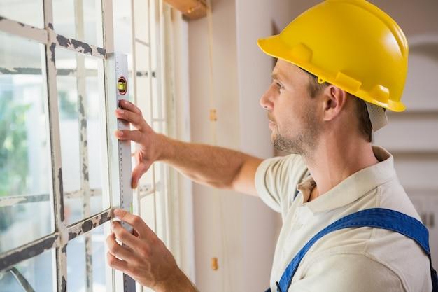 Trabalhador da construção civil usando o nível de espira