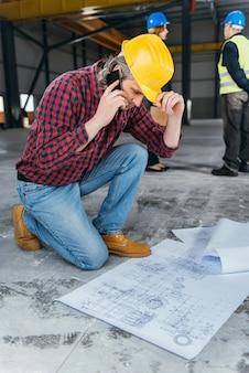 Trabalhador da construção civil verificando blueprints e falando ao telefone