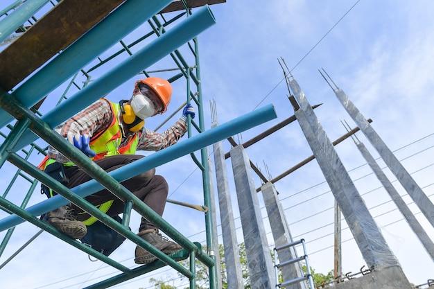Trabalhador da construção civil vestindo segurança trabalhar em alto uniforme em andaimes no canteiro de obras durante o pôr do sol, trabalhando em equipamentos de altura.