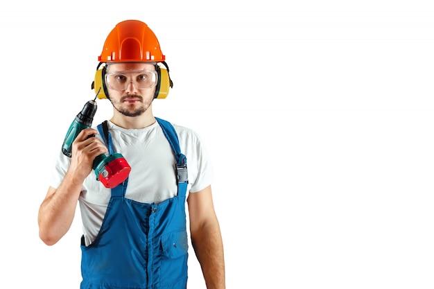 Trabalhador da construção masculino no capacete alaranjado com a chave de fenda isolada no fundo branco.
