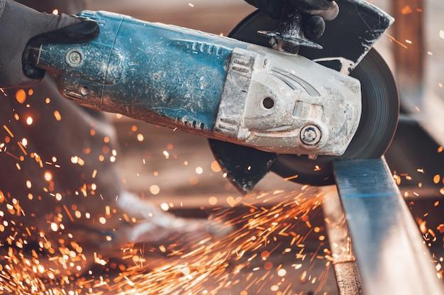 Trabalhador da construção que usa o moedor de ângulo que corta o metal no canteiro de obras.