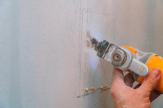 Trabalhador da construção que usa uma ferramenta do sawsall para cortar o drywall uma parede para baixo a uma renovação diy da casa.