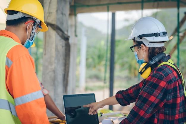 Trabalhador da construção que veste a máscara protetora para proteger contra covid-19 no canteiro de obras, controle de segurança das epidemias no conceito do canteiro de obras.