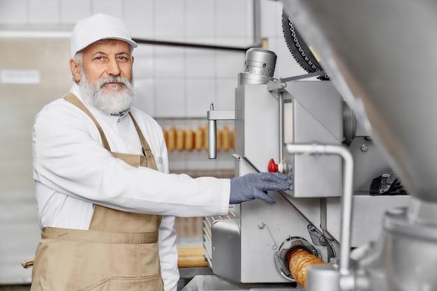 Trabalhador da fábrica de carne posando perto de equipamentos modernos.