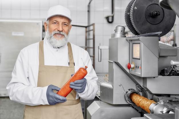 Trabalhador da fábrica de carne segurando salsicha, posando.