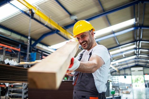 Trabalhador da fábrica verificando o material de madeira para produção futura