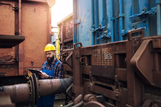 Trabalhador da ferrovia de manutenção de trens verificando vagões e vagões antes da partida