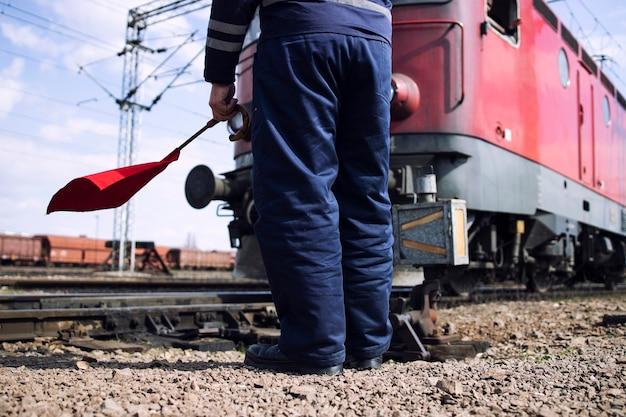 Trabalhador da ferrovia ou switchman com bandeira vermelha em pé pelos trilhos como trem passando na estação.