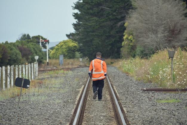 Trabalhador da ferrovia se afastando entre os trilhos