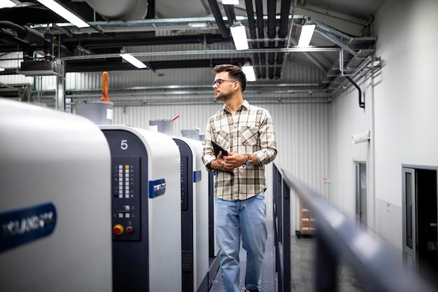 Trabalhador da gráfica controlando o processo de impressão e a qualidade da impressão em uma máquina offset moderna