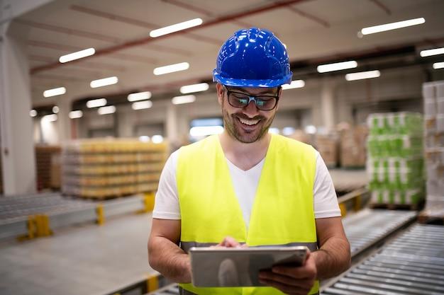 Trabalhador da indústria com jaqueta reflexiva e capacete de segurança olhando para um tablet no interior de uma fábrica moderna