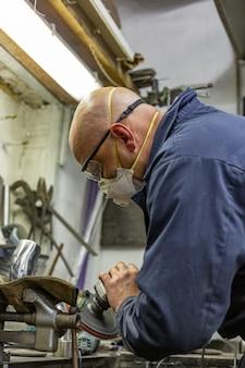 Trabalhador da indústria pesada que corta o aço com a rebarbadora no serviço do carro