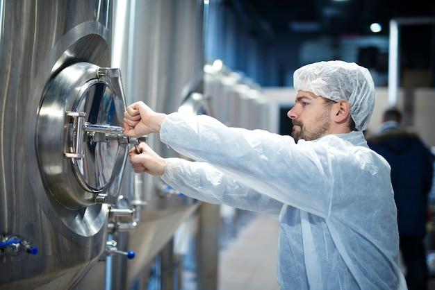 Trabalhador da indústria tecnólogo abrindo a escotilha de uma máquina industrial