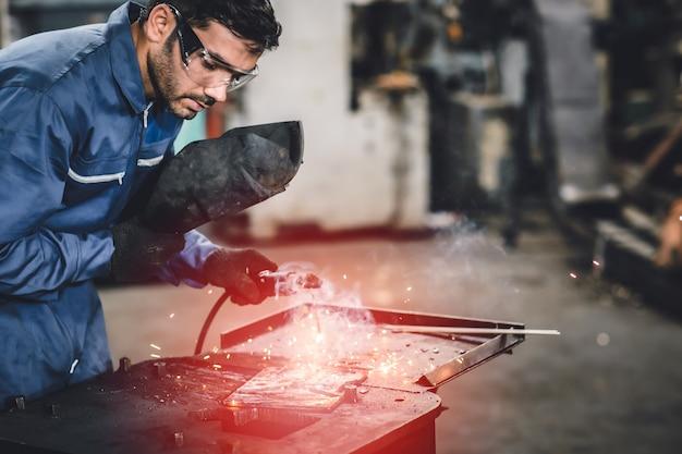 Trabalhador da indústria tig soldando aço com máscara de segurança para proteger a visão na fábrica de metal.