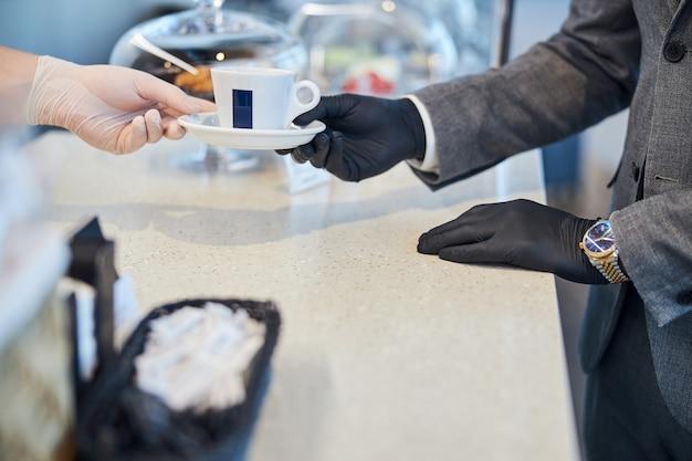 Trabalhador da lanchonete passando uma xícara de café para um comprador