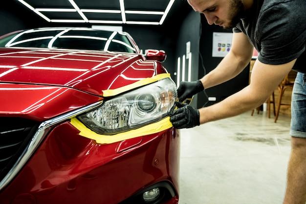 Trabalhador da manutenção automóvel aplicando fita protetora nos detalhes do carro antes de polir
