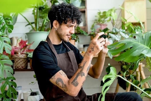Trabalhador da oficina tira uma foto de vasos de plantas