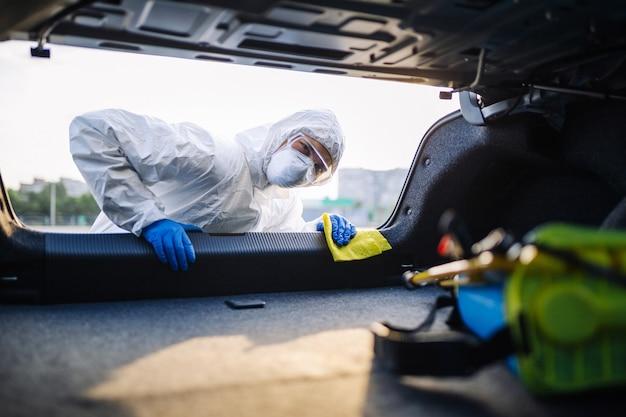 Trabalhador da sanitiry desinfeta o porta-malas do carro