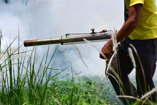 Trabalhador da saúde fumigação que embaça mosquitos portadores do vírus zika da dengue ou malária.