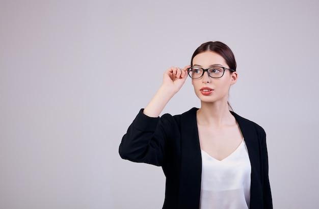 Trabalhador da semana. mulher de negócios de aparência agradável, olhando de lado e de pé em cinza em uma jaqueta preta, camiseta branca e óculos de pc. as mãos da mulher seguram as bordas dos óculos.