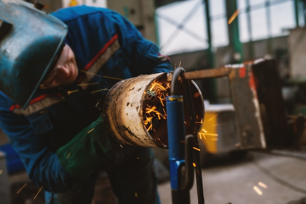 Trabalhador da tela em uniforme de proteção, corte de tubos de metal na mesa de trabalho com um moedor elétrico na oficina industrial.