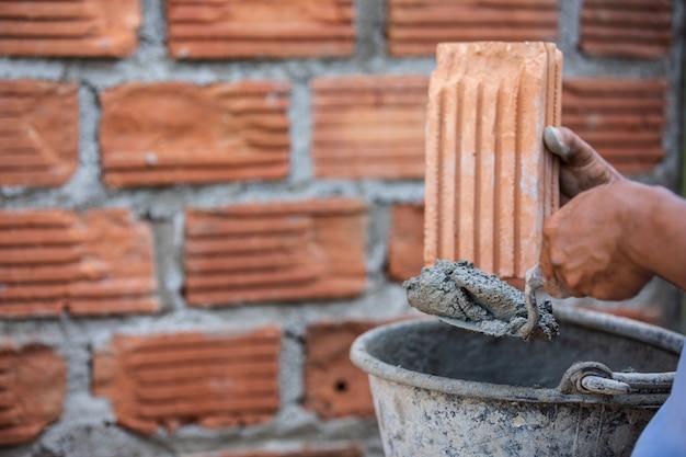 Trabalhador de alvenaria na parede exterior com uma faca da pá de pedreiro.