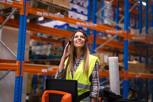 Trabalhador de armazém atraente recebendo instruções por meio de equipamento de fone de ouvido