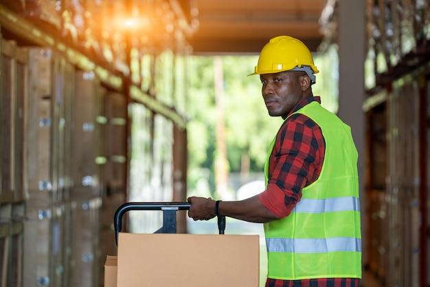 Trabalhador de armazém carregando ou descarregando caixas no armazém,
