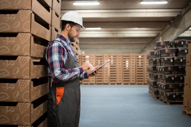 Trabalhador de armazém caucasiano verificando o estoque de mercadorias no computador tablet na sala de armazenamento da fábrica.