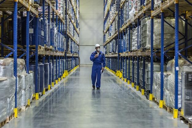 Trabalhador de armazém com produtos de química caminhando entre prateleiras