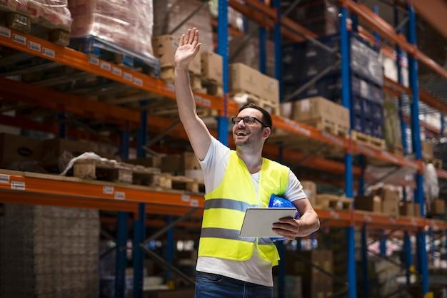 Trabalhador de armazém com tablet e uniforme de proteção em pé entre as prateleiras no centro de armazenamento e acenando para seu colega de trabalho