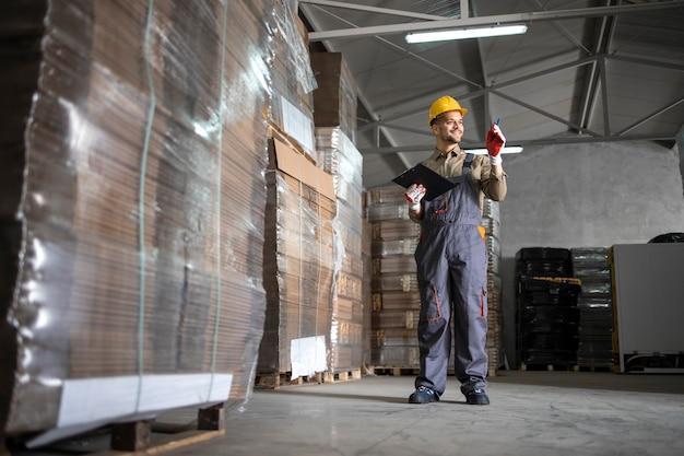Trabalhador de armazém contando paletas no departamento de armazenamento do armazém.