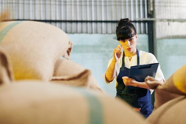 Trabalhador de armazém contando sacos