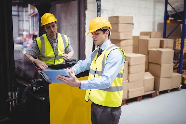 Trabalhador de armazém, conversando com o motorista de empilhadeira em armazém