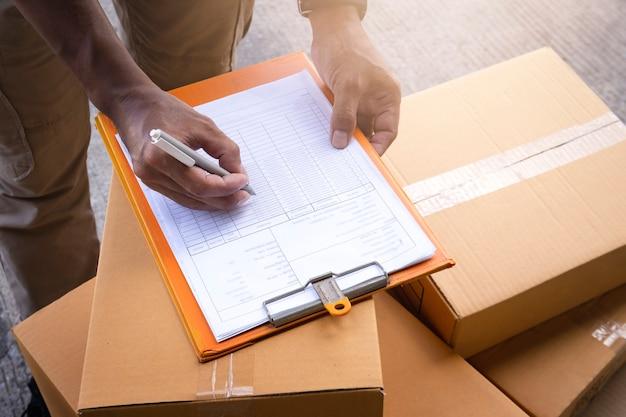 Trabalhador de armazém escrevendo na área de transferência de papel. verificando estoque. gerenciamento de estoque do produto.