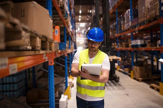 Trabalhador de armazém escrevendo relatório de estoque sobre produtos em grande área de armazenamento