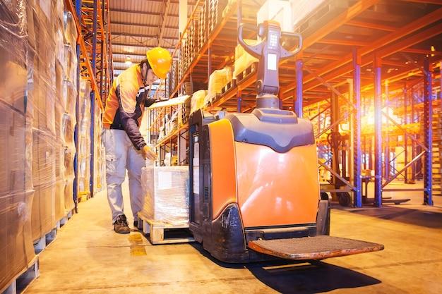 Trabalhador de armazém fazendo gerenciamento de estoque no armazenamento armazém verifique o estoque prateleiras altas armazenamento