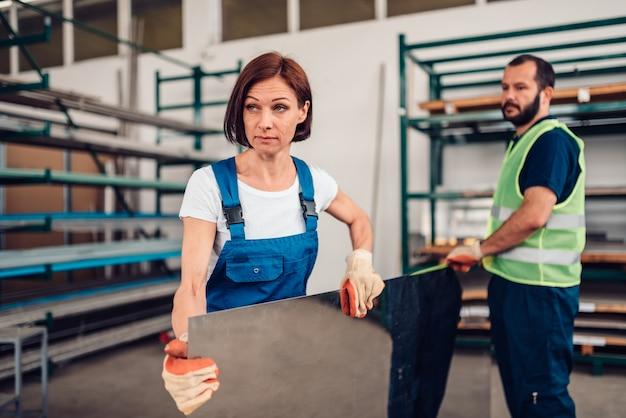 Trabalhador de armazém feminino carregando chapa de aço inoxidável inox