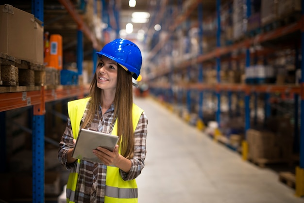 Trabalhador de armazém feminino com tablet contando produtos em prateleiras em grande área de armazenamento