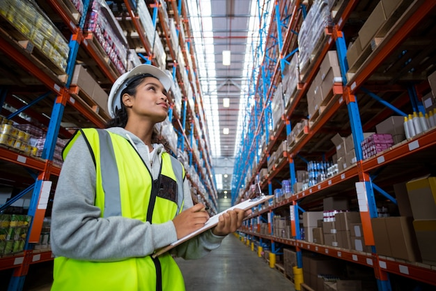 Trabalhador de armazém feminino olhando para pacotes