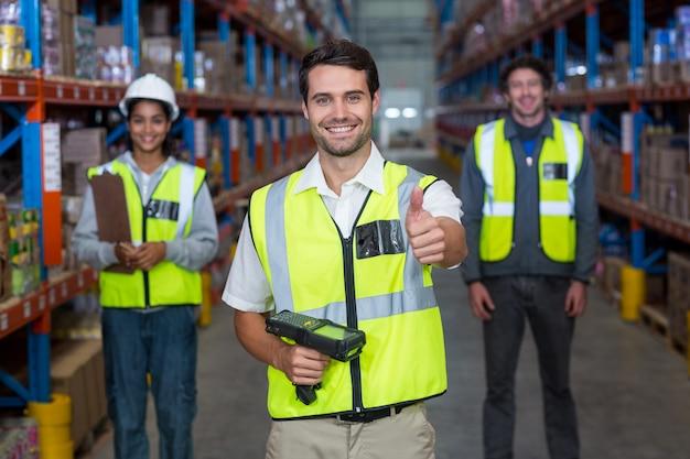 Trabalhador de armazém, mostrando os polegares para cima o sinal
