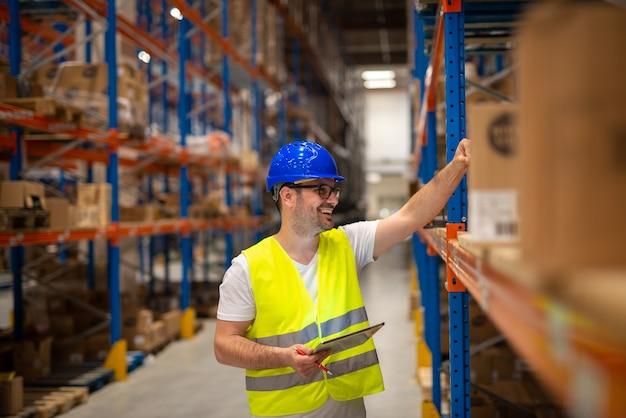 Trabalhador de armazém olhando as prateleiras com pacotes e verificando o estoque da grande área de distribuição de armazenamento de armazém